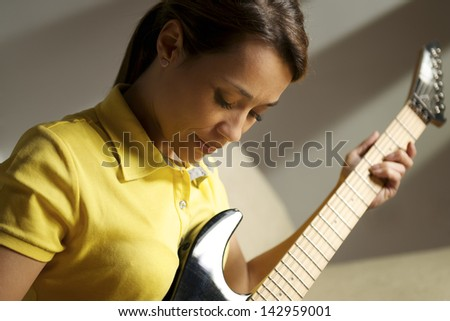 beautiful mid adult woman playing electric guitar at home, sitting on sofa