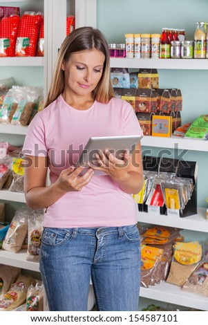 Beautiful mid adult woman using digital tablet in supermarket - stock photo