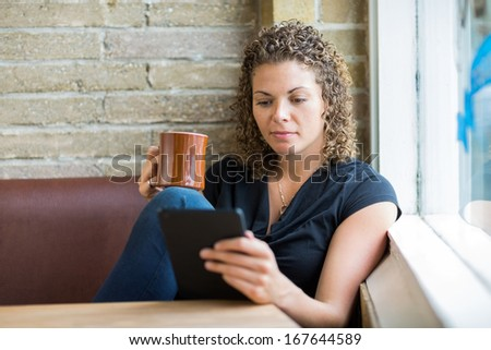 Beautiful mid adult woman using digital tablet while having coffee in cafe - stock photo