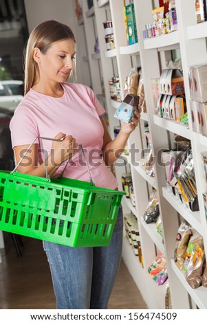 Beautiful mid adult woman with shopping basket choosing product in grocery store - stock photo