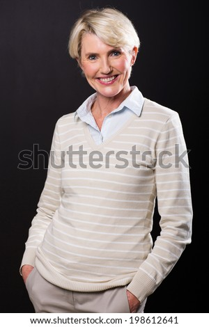 beautiful mid age woman posing on black background - stock photo