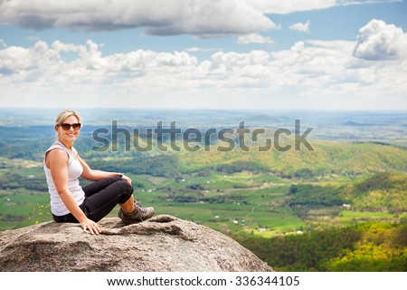 Beautiful mid 30s hiker woman sitting on a rock relaxing in the Shenandoah Valley in Virginia - stock photo