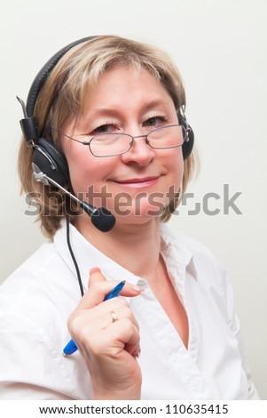 Beautiful middle age blond woman in call center - stock photo