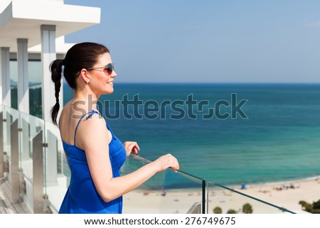 Beautiful middle age woman enjoying the sights of Miami Beach from a balcony. - stock photo