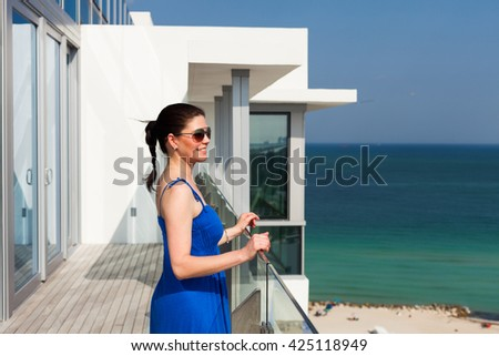 Beautiful middle age woman enjoying the sights of Miami Beach from a balcony.