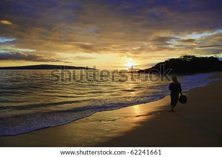 beautiful middle-age woman walking on the shore alone on makena beach, maui at sunset