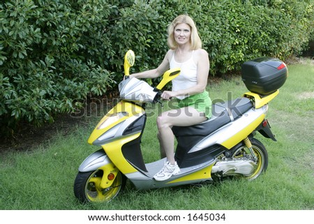 Beautiful Middle-aged Blonde Woman in skimpy green shorts riding a cool yellow 2-seater Motor Scooter. - stock photo
