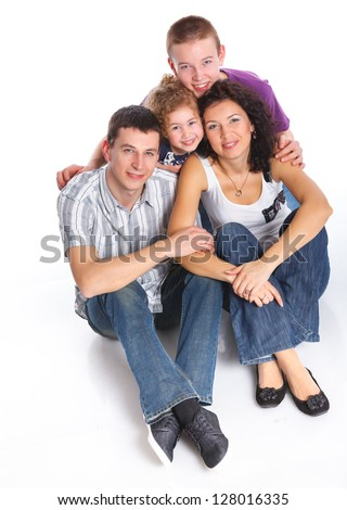 Beautiful middle aged couple carrying cute kids and smiling over white background - stock photo