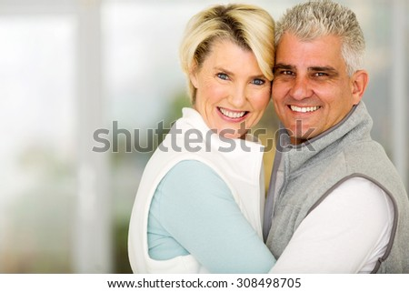 beautiful middle aged couple embracing at home - stock photo