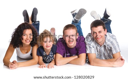 Beautiful middle aged couple lying with cute kids and smiling over white background - stock photo