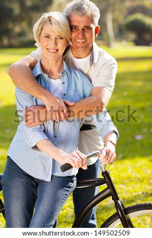 beautiful middle aged couple on bike outdoors