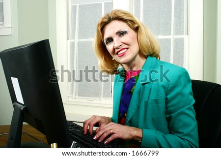 Beautiful middle aged executive business woman smiling and typing on computer in the office.