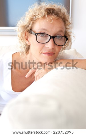 Beautiful middle aged professional woman sitting and relaxing on a white sofa at home with a blank flat screen tv, leaning on her arm being thoughtful and looking away, home interior lifestyle. - stock photo