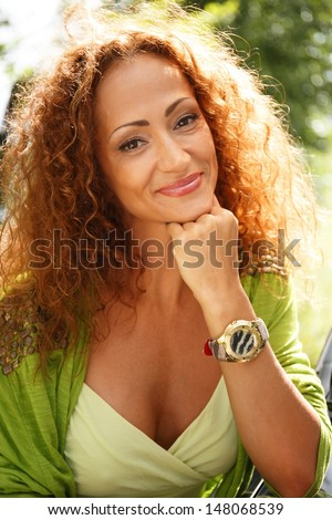 Beautiful middle-aged redhead smiling woman outdoors  - stock photo