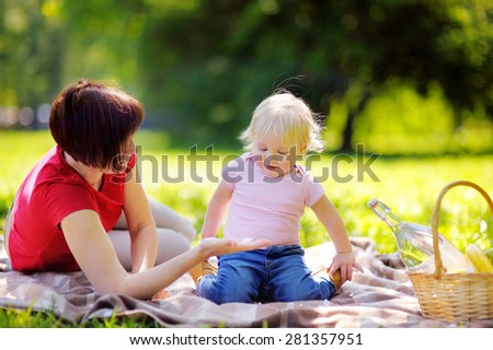 Beautiful middle aged woman and her adorable little grandson having a picnic in sunny park  - stock photo