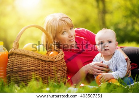 Beautiful middle aged woman and her adorable little son having a picnic in sunny park