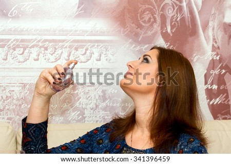 Beautiful middle-aged woman applies perfume, professional make-up.