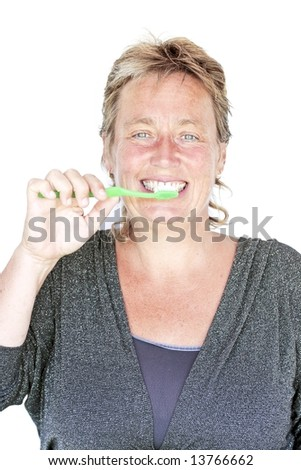 Beautiful middle aged woman brushing her teeth