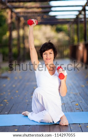 beautiful middle aged woman exercise with dumbbells - stock photo