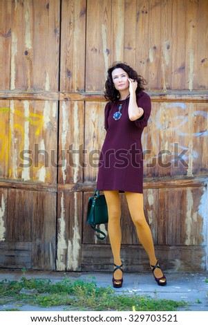 beautiful middle-aged woman in a burgundy dress with a green handbag near the old gate