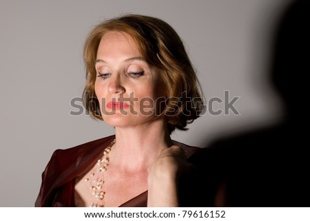 Beautiful middle-aged woman in a red dress. - stock photo