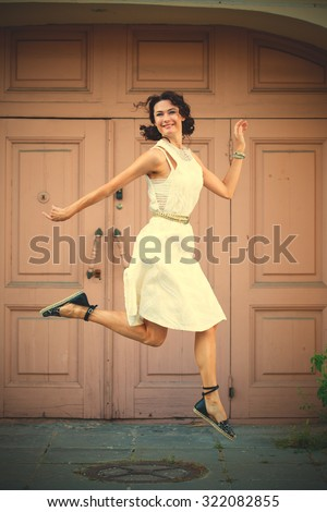 beautiful middle-aged woman in a white dress smiles and jumps near the old door of the ancient house. instagram image filter retro style - stock photo
