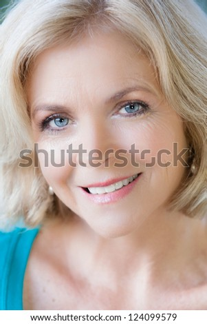 Beautiful Middle Aged Woman in her fifties looking at camera - stock photo