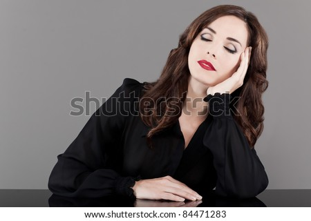 Beautiful middle aged woman sitting at table with eyes closed on gray background - stock photo