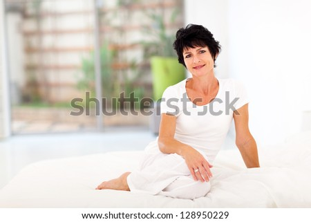 beautiful middle aged woman sitting on bed - stock photo