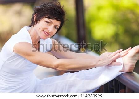 beautiful middle aged woman stretching leg - stock photo
