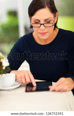 beautiful middle aged woman using tablet computer at home - stock photo