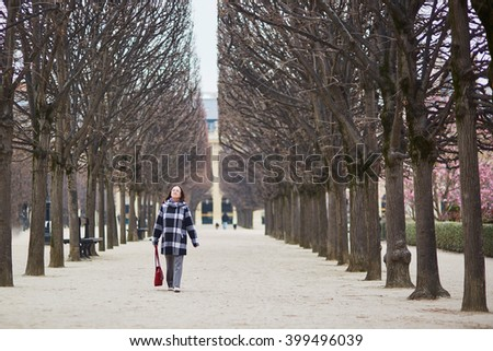 Beautiful middle aged woman walking in Parisian park on a spring day
