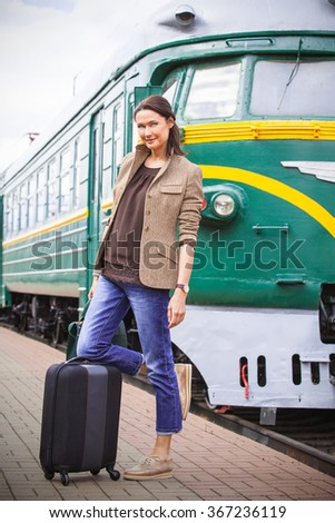beautiful middle-aged woman with luggage on vacation goes retro journey by railway to the old train
