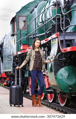 beautiful middle-aged women in retro style travel. she is near ancient train on station platform