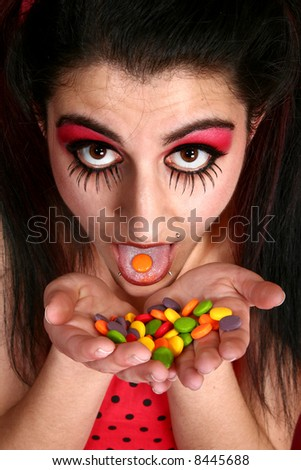 Beautiful Middle Eastern woman in artistic make-up eating colorful candies. - stock photo