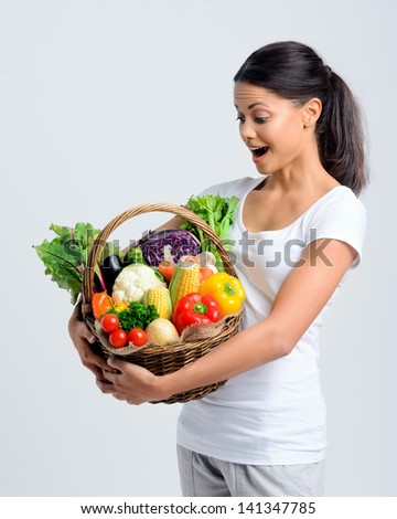 Beautiful mix race woman holding a basket full of fresh organic vegetables with surprised expression - stock photo