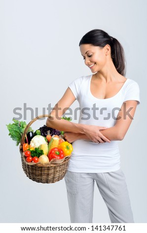 Beautiful mix race woman holding and looking into a basket full of raw organic produce - stock photo