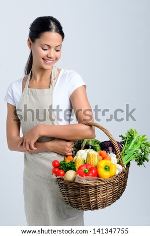 Beautiful mix race woman holding and looking into a basket full of raw organic vegetables - stock photo