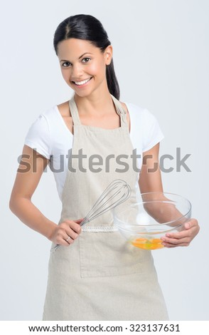Beautiful mix race woman wearing an apron beating eggs