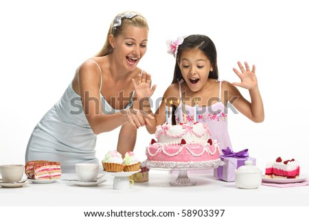 Beautiful mixed family - caucasian mother and her asian daughter celebrate birthday - stock photo