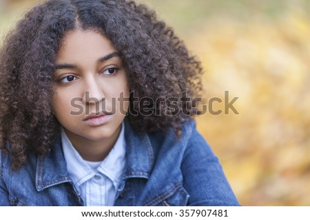 Beautiful mixed race African American girl teenager female young woman outside in autumn or fall looking sad depressed or thoughtful - stock photo