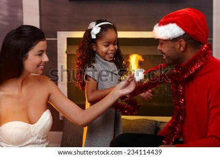 Beautiful mixed race family celebrating christmas at home in living room, smiling, father wearing santa hat. - stock photo