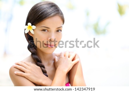 Beautiful mixed race girl natural beauty portrait outdoors on spa resort. Multi-ethnic Asian Caucasian female woman model with perfect skin. Skin care and spa treatment concept portrait. Girl in 20s. - stock photo