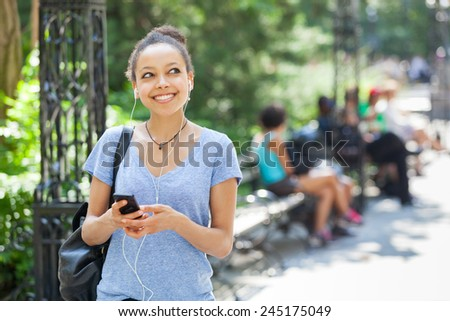 Beautiful Mixed-Race Young Woman Listening Music With Earphones at Park - stock photo