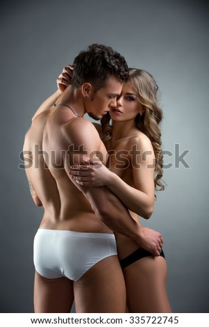 Beautiful model and bodybuilder hugging in studio - stock photo