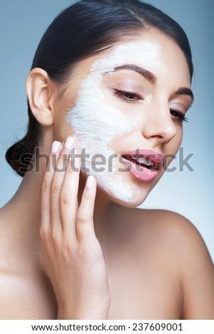 Beautiful model applying mud mask - stock photo