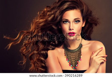 Beautiful model brunette with long curled hair and jewelry necklace .  Hairstyle small Curling  - stock photo