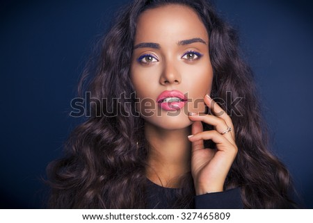 Beautiful model brunette with long curled hair. Purple makeup. Pink lips. Studio shot, horizontal - stock photo