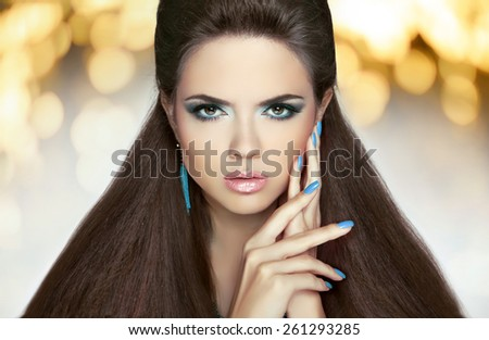 Beautiful model brunette with makeup, long hair. Manicured nails. Hairstyle. Fashion girl over lights holiday background. - stock photo