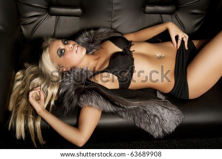 Beautiful model dressed in fur laying on sofa - stock photo